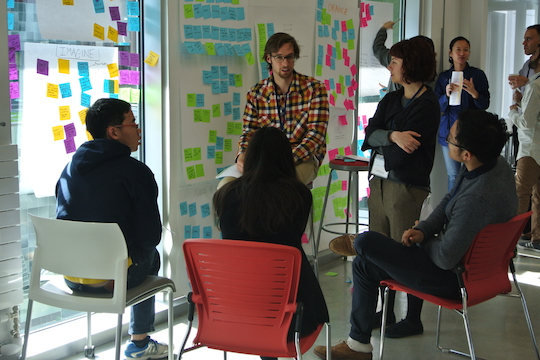 people collaborating around ideas on post-it notes